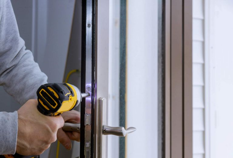 Locksmith hand holds the screwdriver in installing new house door lock